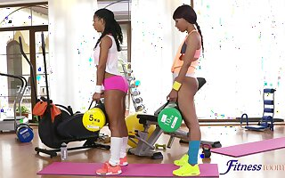 Ebony babes enjoy poking each other's wet pussies on the gym floor