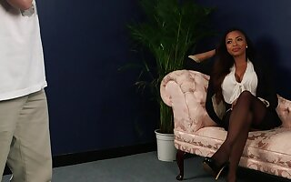 Busty ebony woman sits clothed watching a man jerking off
